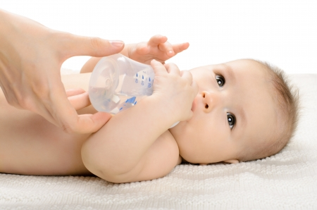 the very  beautiful  little baby drink of  bottle, lie on white background, isolated