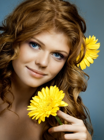 the very  pretty red-haired blue eyed young woman  with yellow flower,  smile , vertical close up portrait photo