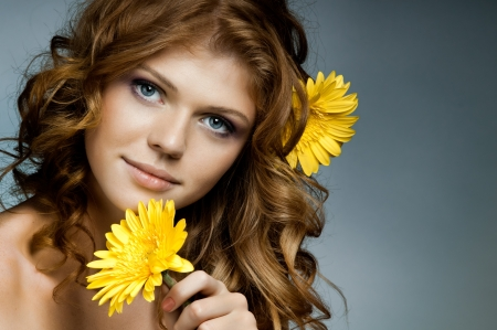 the very  pretty red-haired blue eyed young woman  with yellow flower,  smile , horizontal close up portrait photo
