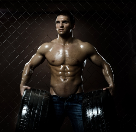 the very muscular handsome sexy guy with rubber-tire,  on  netting  steel fence background Stock Photo