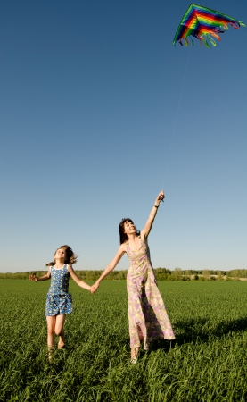 lively: The young girl with  mother quickly runs on a green glade ,  fly a kite and happy smiles