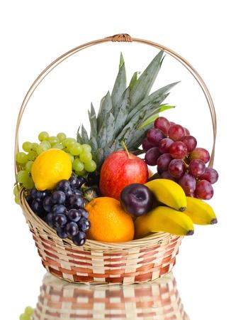 canastas con frutas: bodegón de frutas de varios colores en la cesta grande, sobre fondo blanco, aislado Foto de archivo