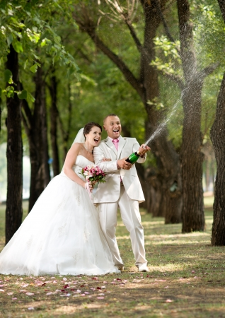 Newly married couple, very happiness and fun, open champagne outdoor in sunny day. Focus on bottle champagne. photo