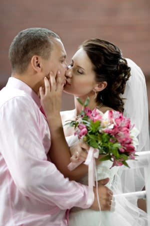 young couple kiss: vertical portrait happy newly married couple , romance embrace and kiss outdoor