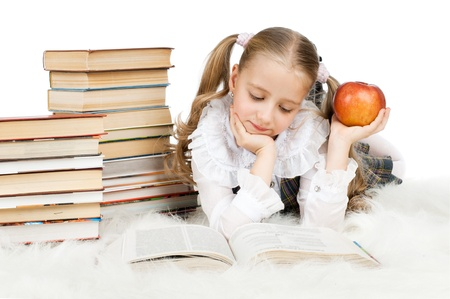 health education: the cute little teen girl lie,  read big textbook, eat apple, on white background, isolated