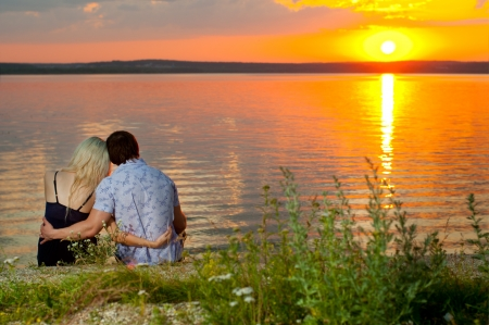 romantic evening date on nature, couple on beautiful sunset on  lake photo