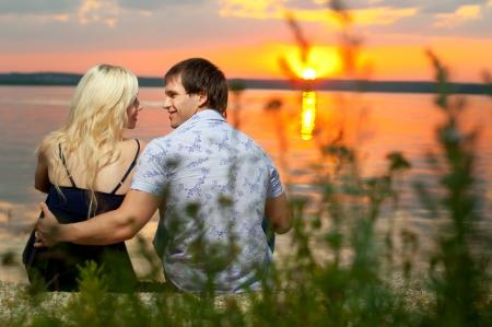 sun rising: romantic evening date on nature, couple on beautiful sunset on  lake