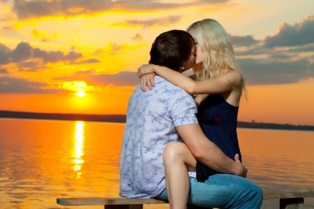 romantic evening date on nature, couple on beautiful sunset on  lake photo