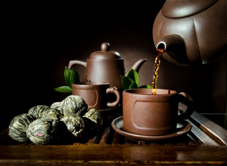 horizontal , of the clay teapot tea flow in  cup on brown background,  tea ceremony photo