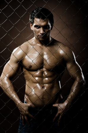 felon: the very muscular handsome sexy guy ,  on  netting   steel fence Stock Photo