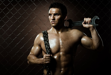the beauty muscular worker  man,  with big wrench and  chain in hands, on netting fence background Stock Photo