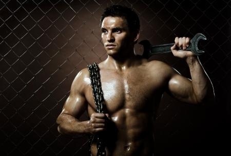 obrero: la belleza del hombre trabajador musculoso, con una llave grande y la cadena en las manos, sobre fondo de compensación valla Foto de archivo