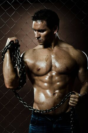 miry:  the beauty muscular worker  man,  with big  chain in hands, on netting fence background Stock Photo