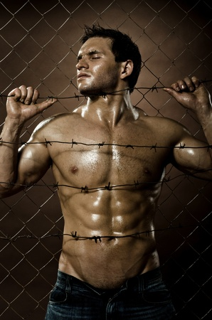 prisoner man: the very muscular handsome felon guy , misery  out of netting   steel fence with  barbed wire Stock Photo