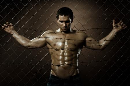 musculoso: el chico guapo delincuente muy musculoso, la miseria de malla de acero valla con alambre de p�as