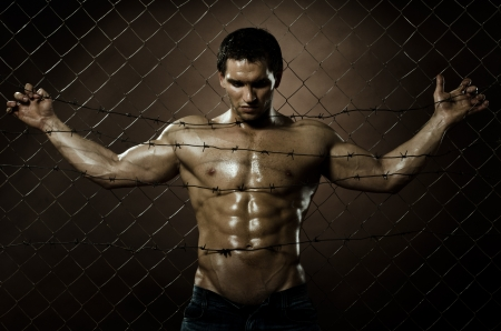 fiend: the very muscular handsome felon guy , misery  out of netting   steel fence with  barbed wire Stock Photo