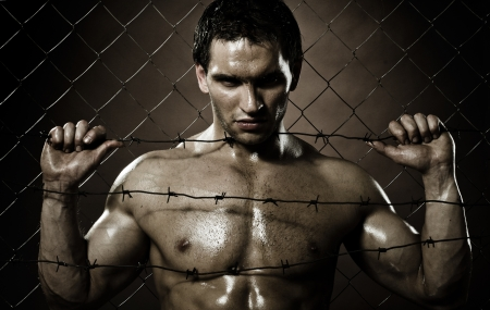 evildoer: the very muscular handsome felon guy ,  out of netting   steel fence Stock Photo