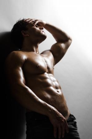 modelos hombres: la muy musculoso chico guapo sexy sobre fondo gris pared Foto de archivo