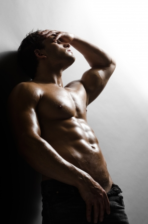 manly: the very muscular handsome sexy guy on   grey wall  background