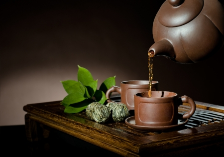 horizontal, of the clay teapot tea flow in  cup on brown background,  tea ceremony photo