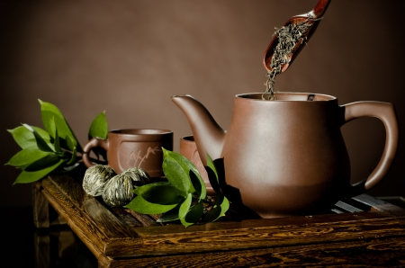 strew: horizontal , tea pour in clay teapot,   on brown background,  tea ceremony