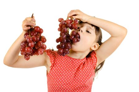 little girl eating bunch of grapes, on white background, isolated photo