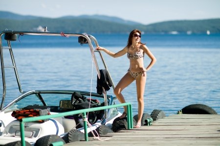 pleasure boat: slender beautiful sexy girl, stand on  moorage  with  motorboat  on water background Stock Photo