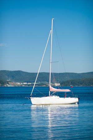 sailingboat: beautiful white sailing yacht , on beauty water landscape background, vertical photo Stock Photo