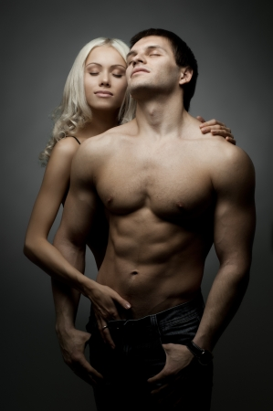 muscularity: muscular handsome sexy guy with pretty woman, on dark background, glamour  light