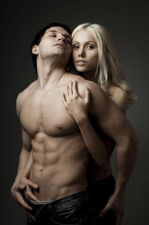 zealous: muscular handsome sexy guy with pretty woman, on dark background, glamour  light