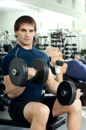 athletic girl and guy,  exercise with dumbbells and smile, in  sport-hall photo
