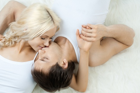 portrait very happy  pretty couple, kiss,  lie on white fur  photo