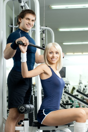 happy cutie athletic girl and guy,  execute exercise on sport-apparatus , in  sport-hall photo