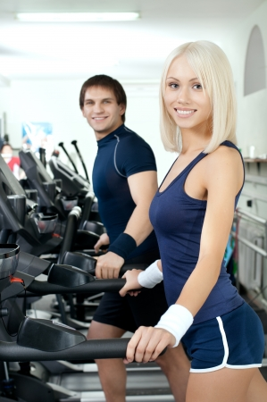 happy cutie athletic girl and guy,  execute exercise on  running track  and smile, in  sport-hall Stock Photo