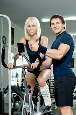 guy instructor,  give instructions cutie girl, about execute exercise on exercise-bicycle, look on camera and smile, in  sport-hall photo