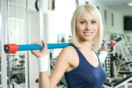 happy cutie athletic girl ,  execute exercise on sport-apparatus  and smile, in  sport-hall photo