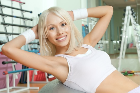 happy cutie athletic girl ,  execute exercise on muscles belly  and smile, in  sport-hall photo