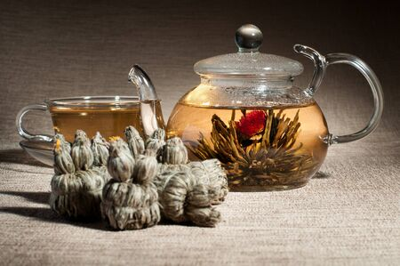 strew: still life of the glass teapot and cup with green tea, on flax-fibre