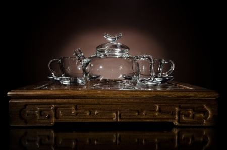 horizontal  photo  of the glass teapot with  cup on  wooden trivet, on dark background photo