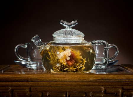 trivet: horizontal  photo  of the glass teapot with green tea in cup on  wooden trivet
