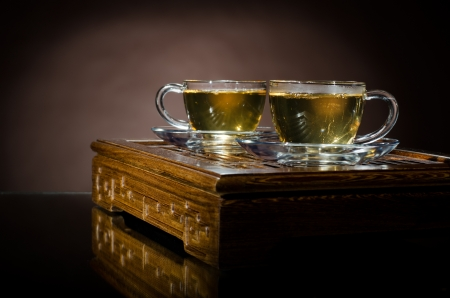 trivet:  still life  of the glass cup with green tea on  wooden trivet, on brown background