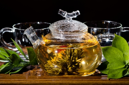 strew: horizontal  photo  of the glass teapot with green tea in cup on  wooden trivet