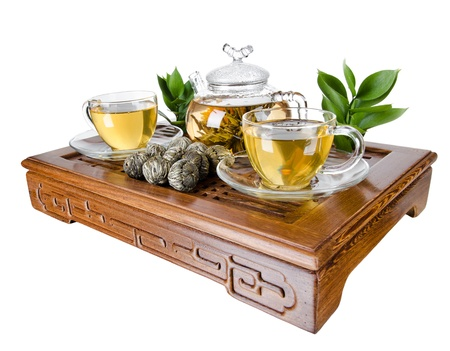 trivet: still life of the glass teapot flow green tea in cup on wooden trivet, white background, isolated,  tea ceremony