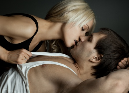 muscular handsome sexy guy with pretty woman, on dark background, kiss Stock Photo