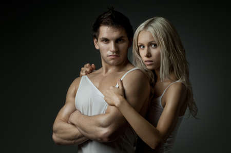 aegis: muscular handsome sexy guy with pretty woman on dark background, look on camera Stock Photo