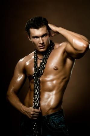 männer nackt: die sehr muskulös schön sexy Kerl auf dunkelbraunem Hintergrund, nackten Oberkörper