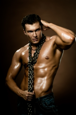 naked man: the very muscular handsome sexy guy on dark  brown background, naked  torso