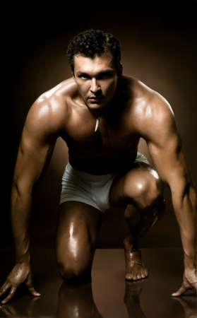 undressed: the very muscular handsome sexy guy on dark  brown background, naked  torso
