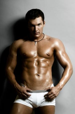 uomo nudo: il bel ragazzo molto muscoloso sexy su sfondo grigio scuro, il torso nudo