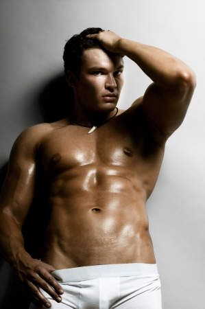 the very muscular handsome sexy guy on dark  grey background, naked torso Stock Photo - 15124943